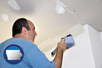 a contractor spackling drywall - with Iowa icon