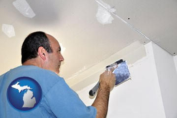 a contractor spackling drywall - with Michigan icon