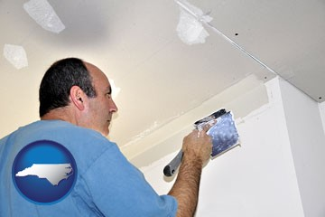 a contractor spackling drywall - with North Carolina icon