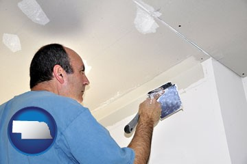 a contractor spackling drywall - with Nebraska icon