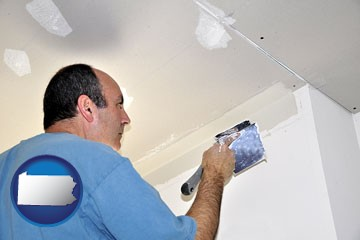 a contractor spackling drywall - with Pennsylvania icon