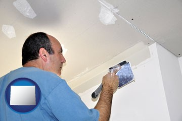 a contractor spackling drywall - with Wyoming icon