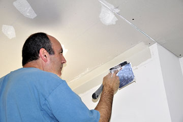 a contractor spackling drywall