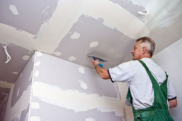 a drywall finisher applying drywall compound on a ceiling